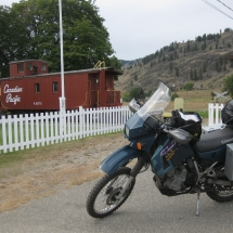 9 Trevor's KLR650 in front of the restored CPR caboose at Midway-Mile Zero of the Kettle Valley Railway